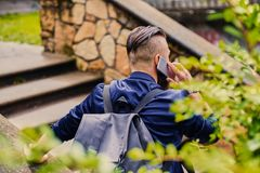 Male speaking by a smartphone. Back view. Traveller male speaking by a smartphone. Back view stock images
