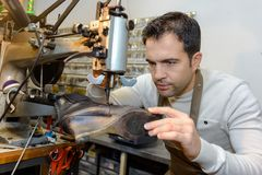 Male specialist fixing heel taps shoes on machine. Male specialist fixing heel taps of shoes on machine Stock Images