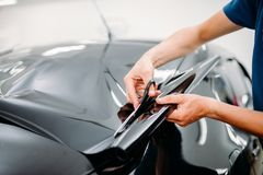 Male specialist with scissors, car tinting film. Installation process, tinted auto glass installing procedure Stock Images