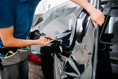 Male specialist with scissors, car tinting film. Installation process, tinted auto glass installing procedure Royalty Free Stock Image