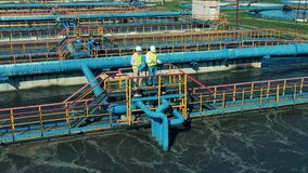 Male specialists talking at a wastewater treatment plant