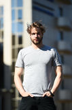 Male sport fashion, people outdoor, casual style and fashionable lifestyle. Bearded man or handsome guy in grey shirt, has stylish hair sunny outdoor on blurred Stock Image