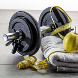 Male sport lifestyle with weights and measuring tape at gym. Male sport lifestyle with still-life of weights, grey towel, measuring tape and apple for fit Stock Photography