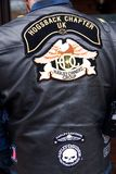 Male in black leather biker jacket with Harley Davidson patches. Male, sporting a black leather biker jacket, decorated with embroidered Harley Davidson patches royalty free stock image