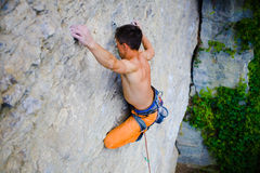 Male sports and climbs on the rock. Athletic man climbing the mountains, playing sports in nature Stock Image