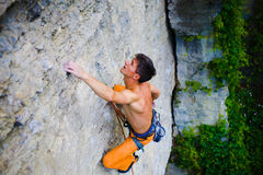 Male sports and climbs on the rock. Athletic man climbing the mountains, playing sports in nature Stock Photography