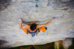 Male sports and climbs on the rock. Athletic man climbing the mountains, playing sports in nature Royalty Free Stock Photo
