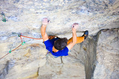 Male sports and climbs on the rock. Athletic man climbing the mountains, playing sports in nature Royalty Free Stock Images