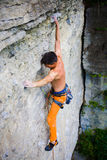 Male sports and climbs on the rock. Athletic man climbing the mountains, playing sports in nature Royalty Free Stock Image