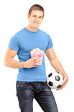 Male sports fan holding a football and popcorn box. Isolated on white background Royalty Free Stock Photography