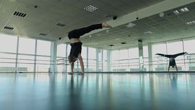 Male sportsman at dance studio making handstand with legs spread out. Male athlete making handstand at dancing studio with legs spread out. Young person stock video