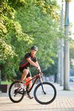 Male sportsman posing on bike near green trees. Toned sportsman cycling on bicycle near green park. Cyclist shooting for clothing advertisement campaign. Concept Stock Photography