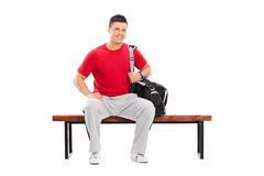 Male sportsman sitting on a wooden bench Royalty Free Stock Photos