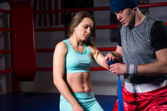Male sporty boxer preparing bandages for athletic female. In regular boxing ring in a gym Stock Photography