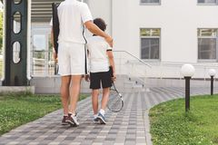 Male sporty members of family walking to building. Father is putting hand on son shoulder. They are turning back and on way home. Boy carrying tennis racket Stock Image