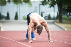 Male Sprinter Getting Ready to Start the Race. Athletic Man on Running Track Getting Ready to Start Run Royalty Free Stock Photo