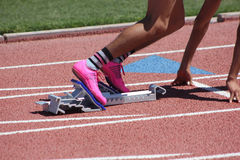 Male sprinter in starting block pink shoes. A male sprinter prepares for his race in the starting blocks while wearing pink cleets and striped socks. Taken at Stock Image