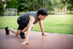 Male sprinter starting on the running track. Young Asian athlete runner man getting ready for start running in the park. Male sprinter starting on the running Royalty Free Stock Images