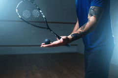 Male squash player training on indoor court. Male squash player with racket training on indoor court. Active sport with racquet and ball Stock Photo