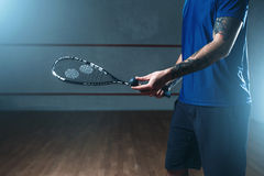 Male squash player training on indoor court. Male squash player with racket training on indoor court. Active sport with racquet and ball Stock Photos