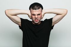 Male squinting with force to back away from what is happening. A male in a black t-shirt against grey studio background that doesn't want to hear anything from Stock Image