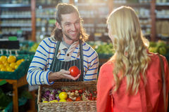Male staff assisting woman in selecting fresh vegetables. Male staff assisting women in selecting fresh vegetables in supermarket Royalty Free Stock Photography
