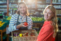 Male staff assisting woman in selecting fresh vegetables. Male staff assisting women in selecting fresh vegetables in supermarket Royalty Free Stock Image