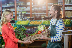 Male staff giving a crate of fresh vegetables to woman in organic section. Male staff giving a crate of fresh vegetables to women in organic section of Stock Photo