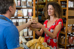 Male staff giving packed bread to woman. Male staff giving packed bread to women in supermarket Royalty Free Stock Images