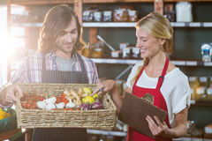 Male staff holding basket of vegetables and female staff with clipboard. In supermarket Royalty Free Stock Photos