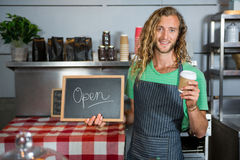Male staff holding a board with open sign and disposable coffee cup. Portrait of male staff holding a board with open sign and disposable coffee cup in coffee Royalty Free Stock Images
