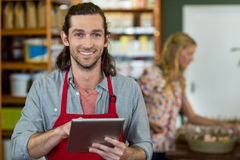 Male staff holding a digital tablet and checking grocery products on the shelf. Portrait of smiling male staff using a digital tablet in supermarket Royalty Free Stock Images
