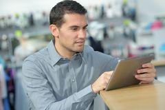 Male staff holding digital tablet and checking product. Male staff holding a digital tablet and checking a product Royalty Free Stock Photo