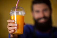 Male staff holding orange juice glass at organic section. Of supermarket Royalty Free Stock Image