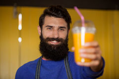 Male staff holding orange juice glass at organic section. Of supermarket Royalty Free Stock Photos