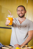 Male staff holding orange juice glass at organic section. Of supermarket Stock Image