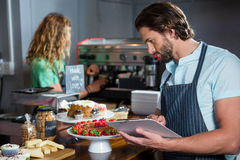 Male staff maintaining a record on clipboard at counter. In coffee shop Stock Images