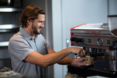 Male staff making cup of coffee at counter. In shop Royalty Free Stock Images