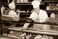 Male staff offering fresh pastry. Mature male staff offering fresh cakes in sweet-shop Stock Photo