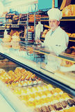 Male staff offering fresh pastry. Mature male staff offering fresh pastry in culinary Royalty Free Stock Image