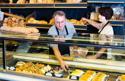 Male staff offering fresh pastry. Mature smiling male staff offering fresh pastry in sweet-shop Stock Images