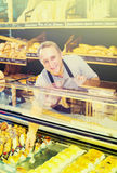 Male staff offering fresh pastry. Mature male staff offering fresh pastry in supermarket Stock Images