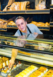 Male staff offering fresh pastry. Mature male staff offering fresh pastry in sweet-shop inside Stock Photos