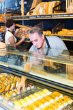 Male staff offering fresh pastry. Portrait of mature male staff offering fresh pastry in sweet-shop Stock Photos