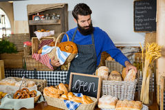 Male staff picking up bread from a wicker basket at counter. In bakery shop Royalty Free Stock Photos