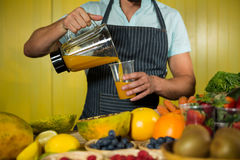 Male staff pouring juice into glass at counter. In health grocery shop Royalty Free Stock Photos
