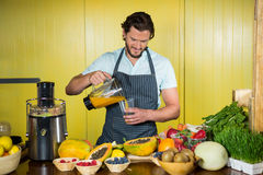 Male staff pouring juice into glass at counter. In health grocery shop Stock Photos