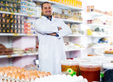 Male staff standing near containers with olives. Shop staff standing near containers with olives in flavoured brine Stock Photo