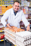 Male staff standing near containers with olives. Shop staff standing near containers with olives in flavoured brine Stock Image