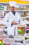 Male staff standing near containers with olives. Shop staff standing near containers with olives in flavoured brine Royalty Free Stock Photography